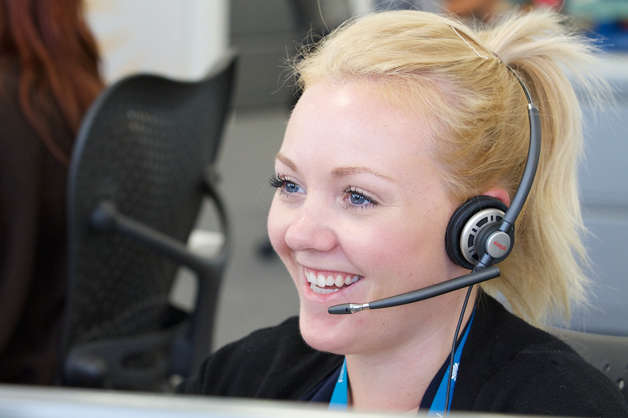Smiling-call-centre-advisor-with-earpiece