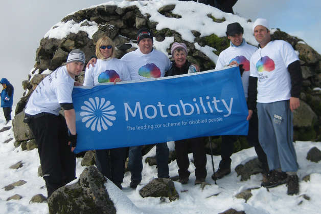 Motability-employees-holding-Motability-banner-on-top-of-mountain