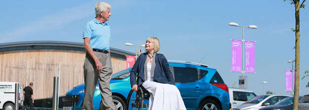 Lady-in-wheelchair-in-front-of-blue-car-with-partner